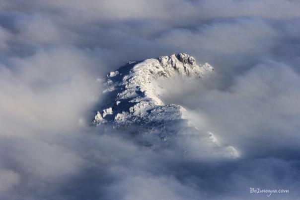 High Mountain Snow Caps Peeking Through the Clouds